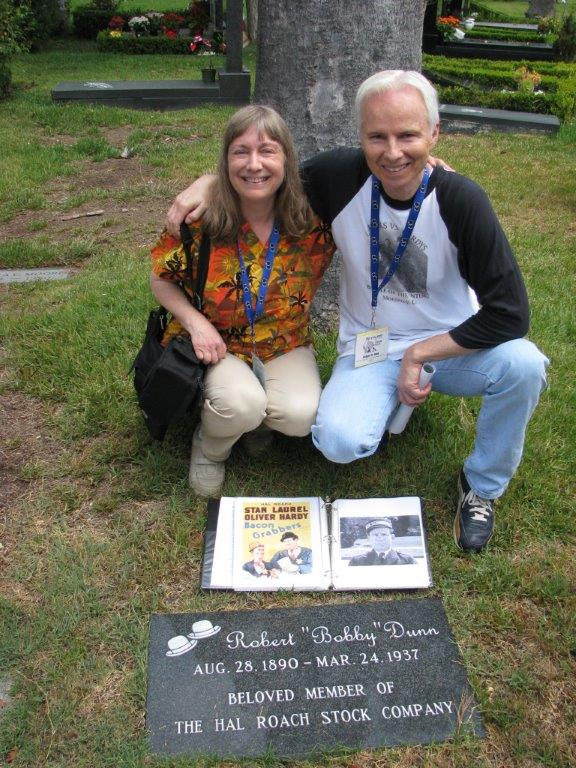 At Hollywood Forever Marcia Opal and Richard Bann pose in front of Bobby Dunn's marker. The grave stone for Bobby Dunn was placed in the last few years as he was buried in an unmarked grave after passing away at the Motion Picture Home.