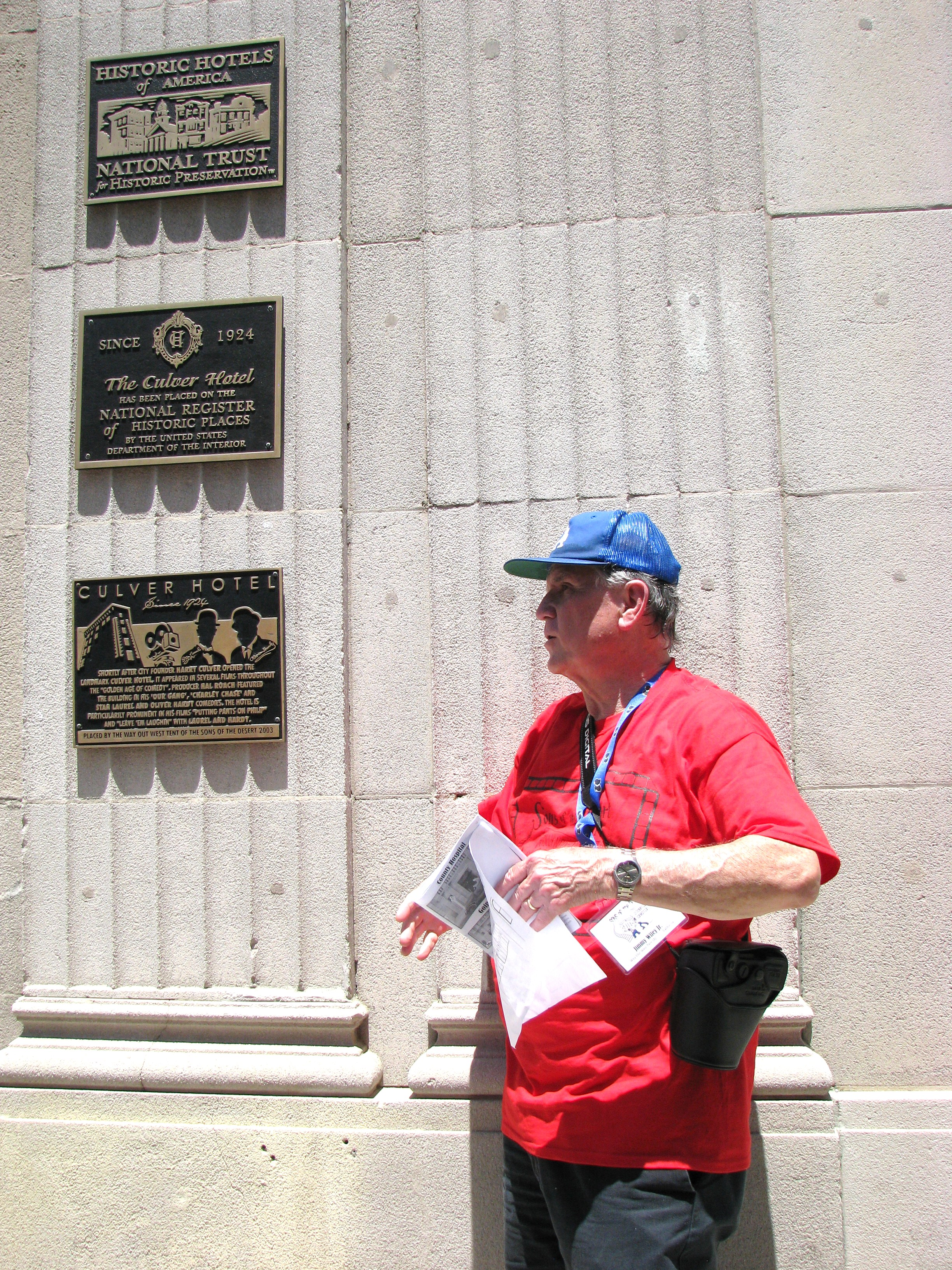 Tour guide Jimmy Wiley shows the historic plaques outside the Culver Hotel, one which was placed by the Way Out  West Tent